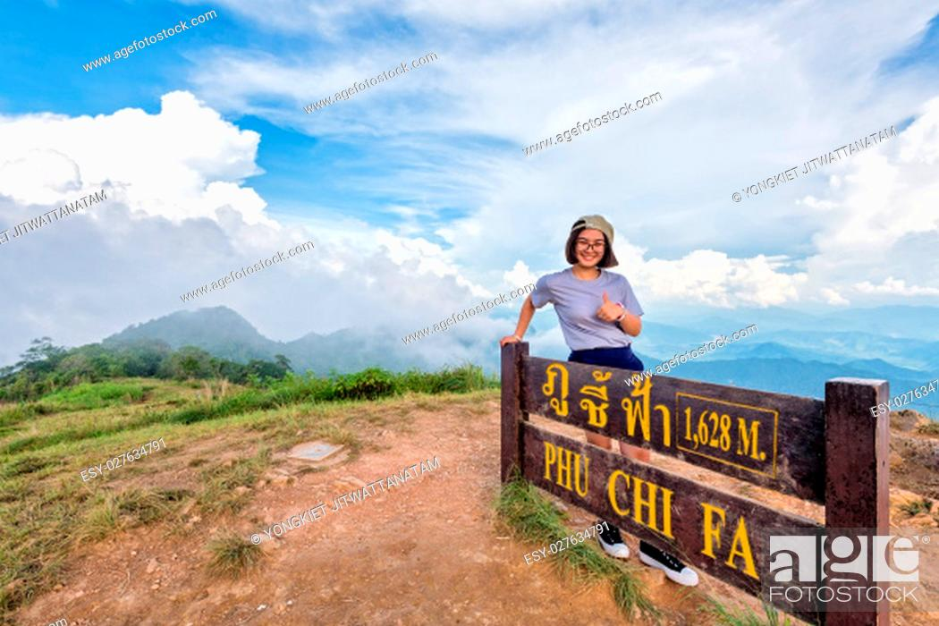 Imagen: Tourist teen girl hiker wear cap and glasses standing smile pose thumb up near nameplate attractions of Phu Chi Fa Forest Park on mountain and blue sky.