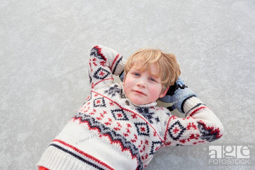 Stock Photo: Overhead portrait of boy lying on frozen lake, Gavle, Sweden.