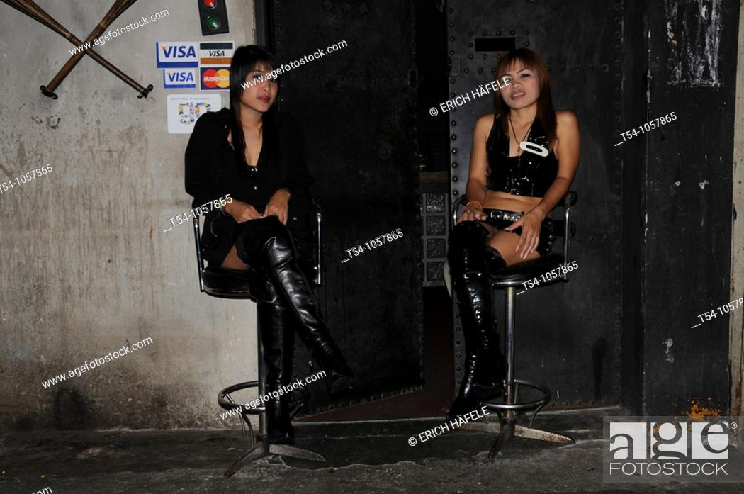 Stock Photo: Two Asian Dominas sitting infront of a Club in Bangkok.