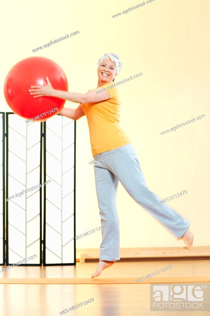 Stock Photo: Senior woman holding gymnastic ball, portrait.