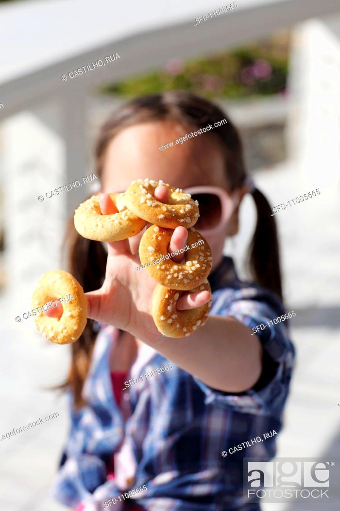 Photo de stock: A little girl with mini sweet bread rings.