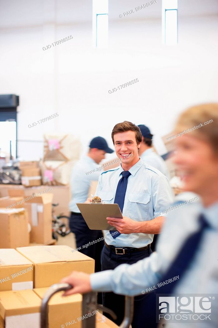 Stock Photo: Worker writing on clipboard in shipping area.