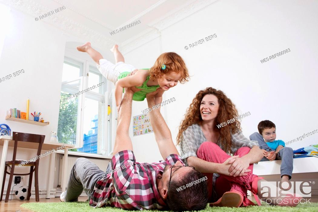 Stock Photo: Germany, Berlin, Father holding daughter, mother sitting besides.