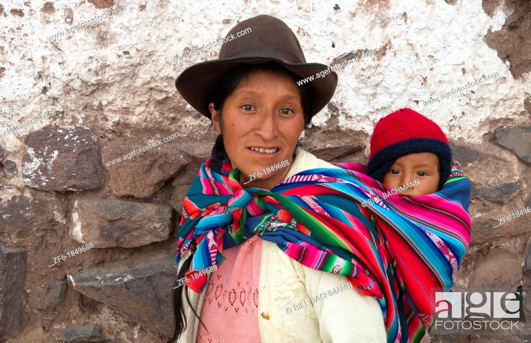 Stock Photo: Traditional woman in dress and hat with baby on back in small town of Pisaq Peru.