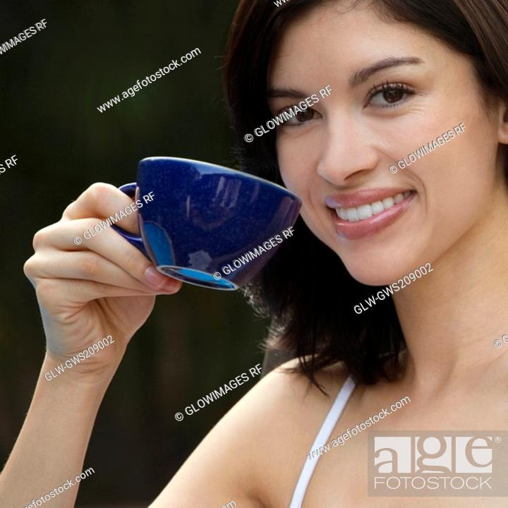 Stock Photo: Portrait of a young woman holding a cup of tea and smiling.