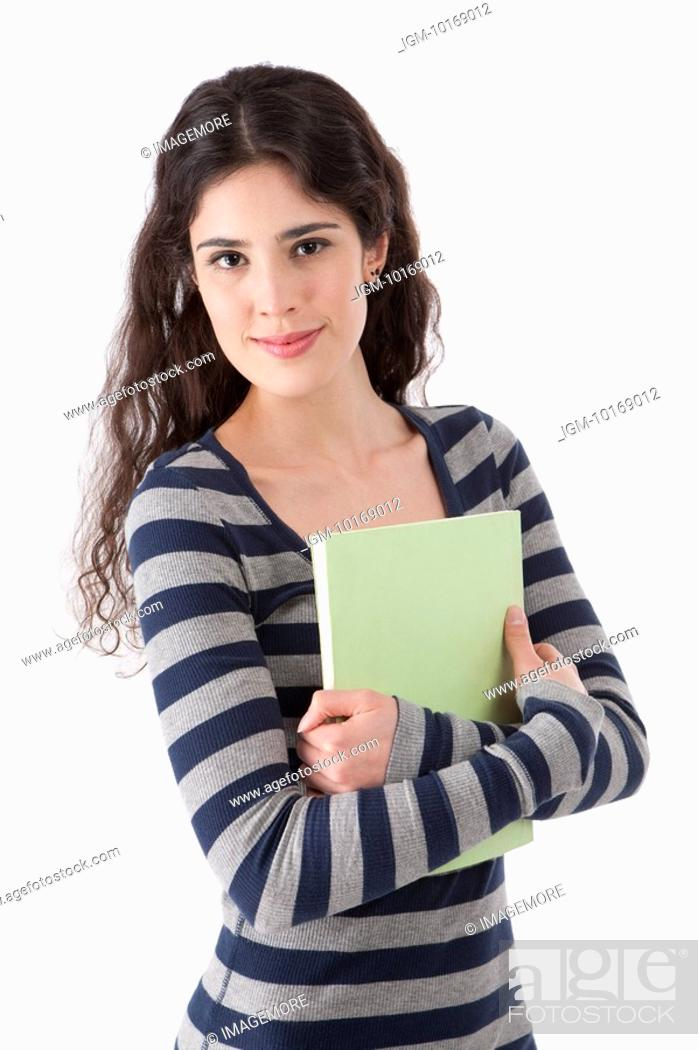 Stock Photo: Young woman holding a book, smiling.