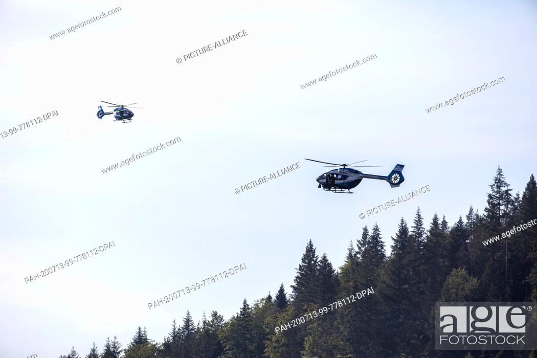 Stock Photo: 13 July 2020, Baden-Wuerttemberg, Oppenau: Two police helicopters fly over the forest near the community of Oppenau. With a large contingent.