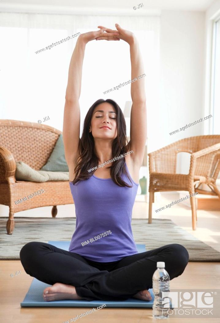 Stock Photo: Hispanic woman doing yoga in living room.