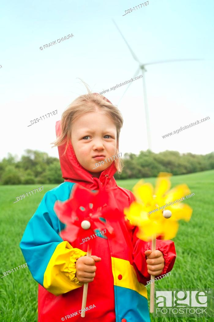 Stock Photo: boy in colorful raincoat holding pinwheel standing in front of wind turbine.