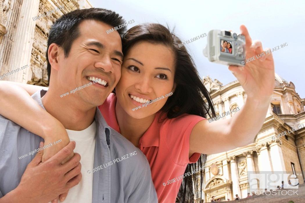 Stock Photo: Asian couple taking own photograph.