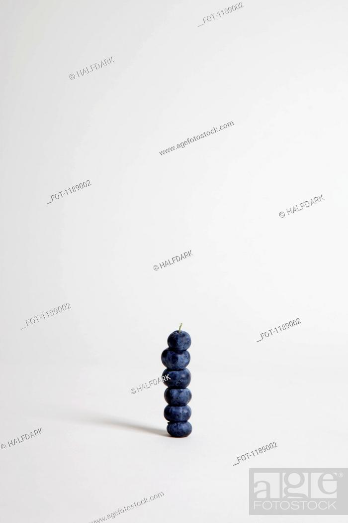 Stock Photo: Blueberries arranged into a stack, studio shot.