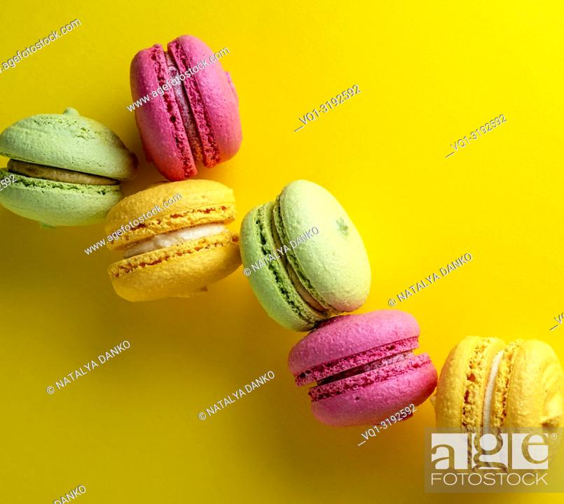 Imagen: multicolored round macarons almond flour cakes on a yellow background.