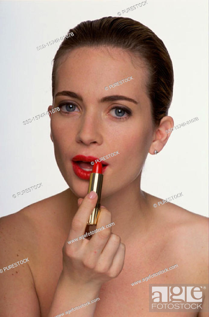 Stock Photo: Portrait of a young woman applying lipstick.