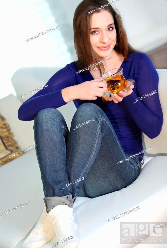 Stock Photo: woman sitting on sofa drinking tea.