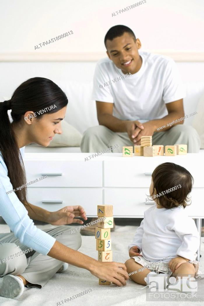 Stock Photo: Mother and toddler girl playing with building blocks, daughter looking over shoulder at father in background.