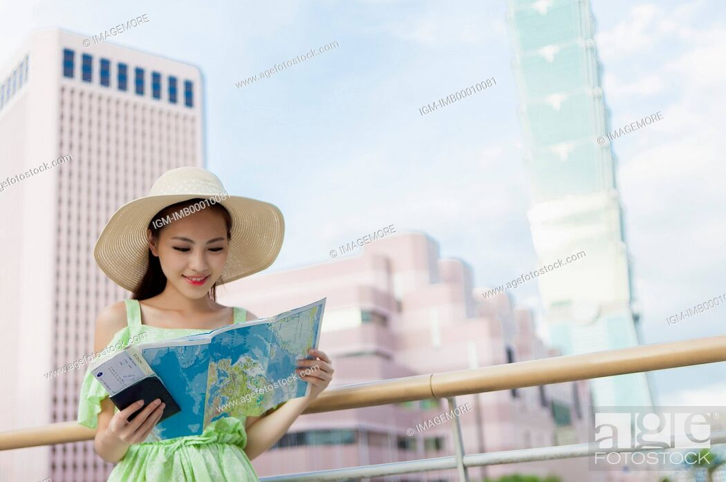 Stock Photo: Young woman holding a map and looking down with smile.