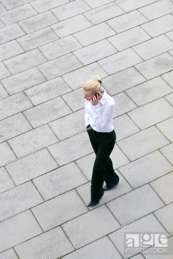 Stock Photo: Businesswoman talking on phone as she walks.