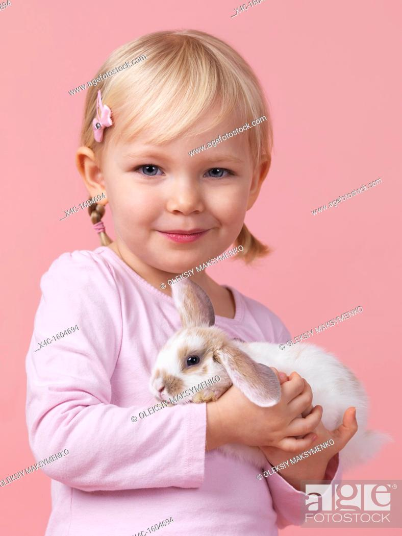 Stock Photo: Portrait of a three year old smiling girl holding a pet rabbit in her hands isolated on pink background.