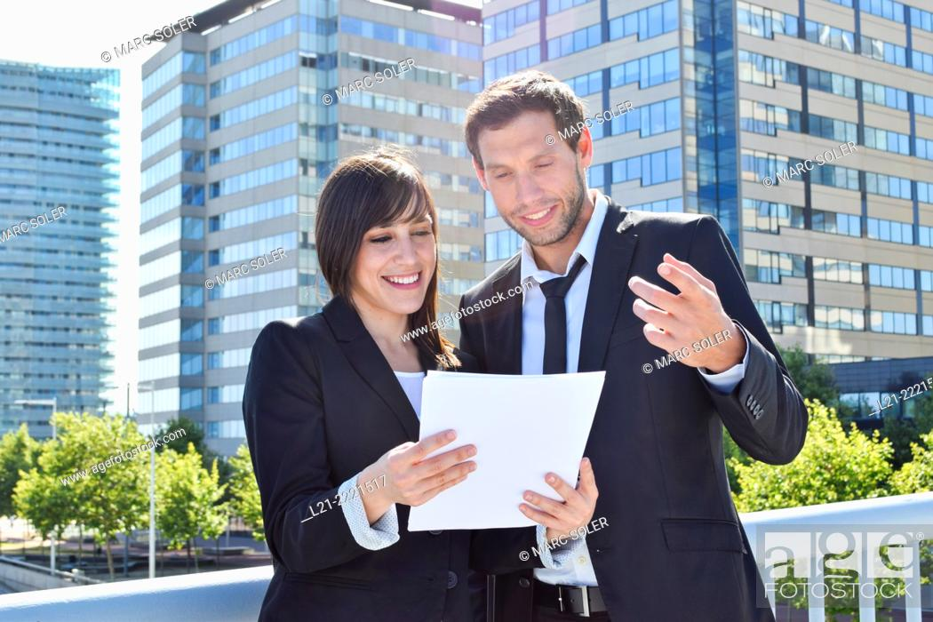 Stock Photo: Businessman and businesswoman look over paperwork while standing outside.