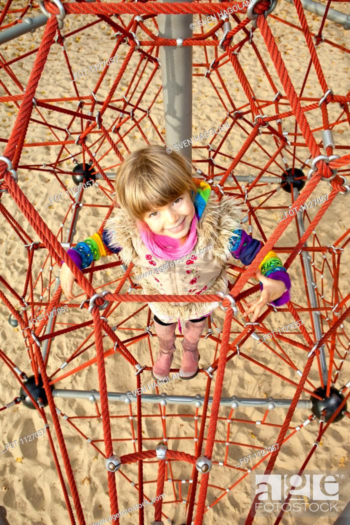 Stock Photo: Girl on jungle gym looking up.