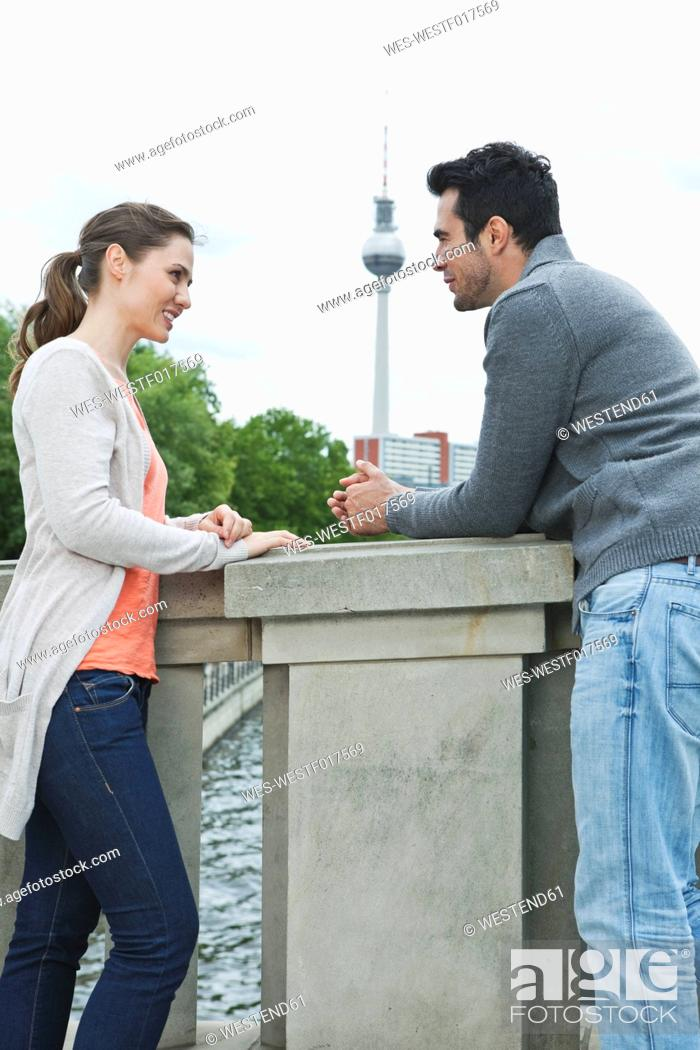Stock Photo: Germany, Berlin, Couple standing on bridge and talking.