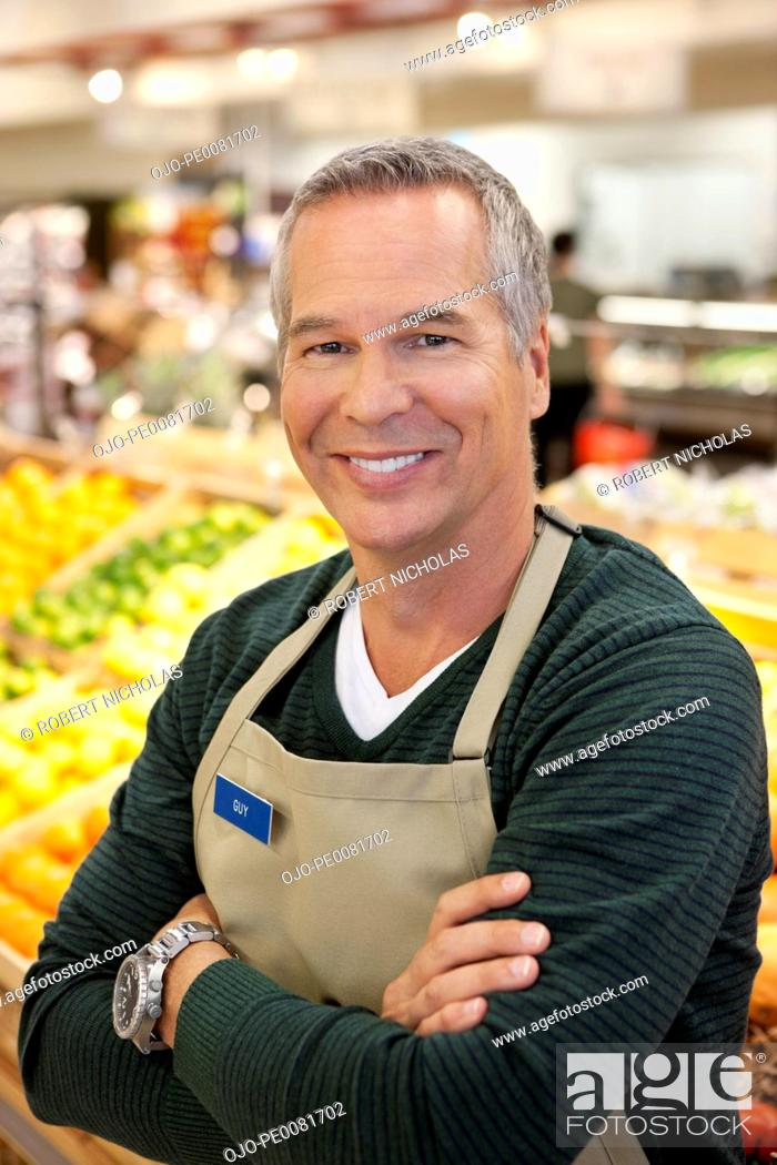 Stock Photo: Worker smiling in supermarket.