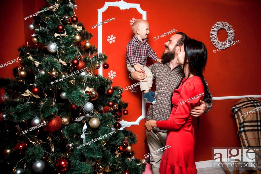 Stock Photo: Christmas family portrait in home holiday living room, baby with parents, decorating house with Xmas tree and gifts.