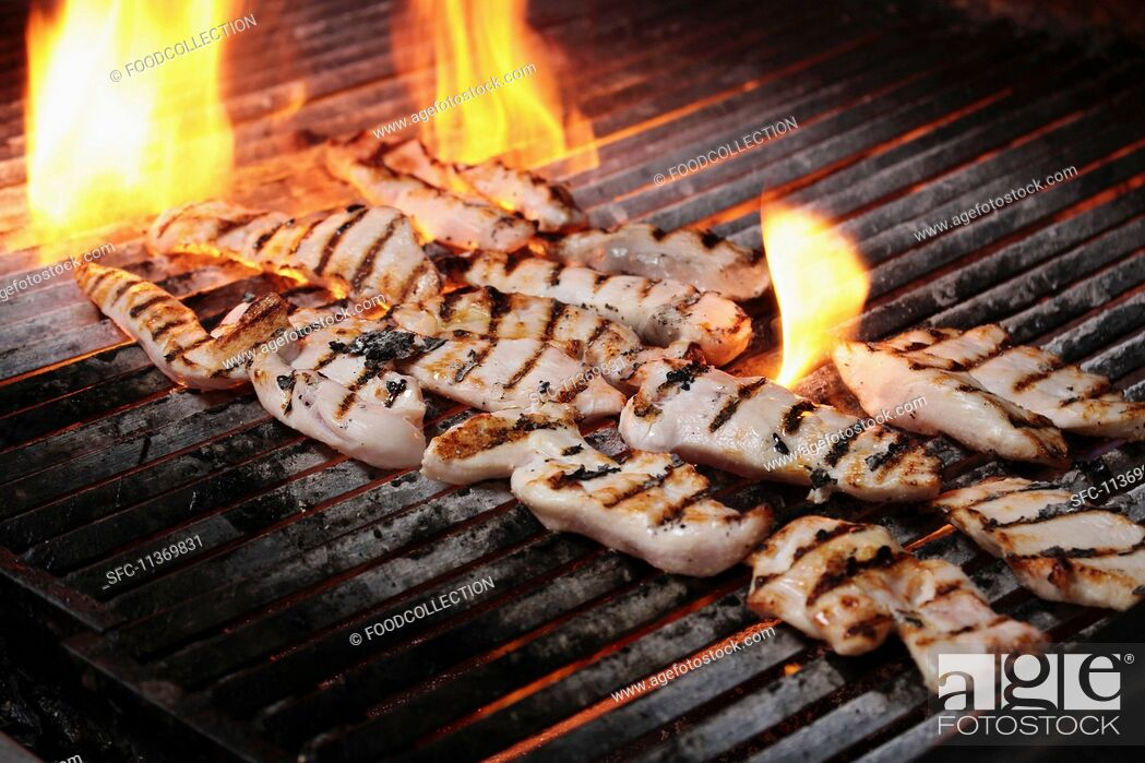 Imagen: Chicken fillets on flaming a charcoal grill.
