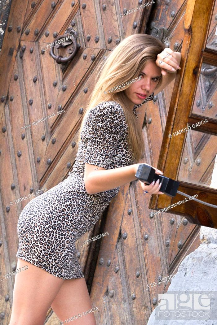Imagen: Sexy and elegant Ukrainian woman wearing a leopard-skin print dress posing reclining to a telephone booth for a photographic sequence in the ancient city of.