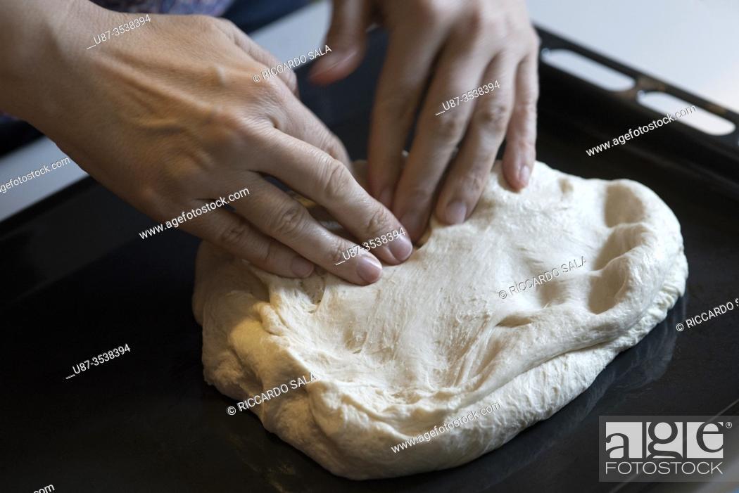 Stock Photo: Pressing Pizza Dough Into Oven Tray. . .