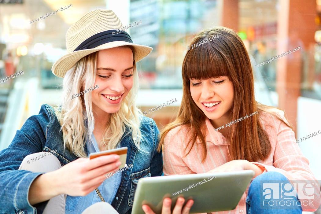Stock Photo: Zwei Teenager mit Kreditkarte und Tablet Computer beim online Shopping.