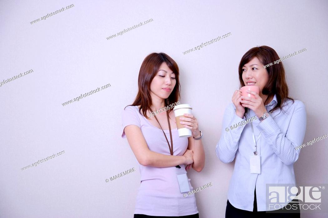 Stock Photo: Two women drinking coffee at coffee break and smiling.