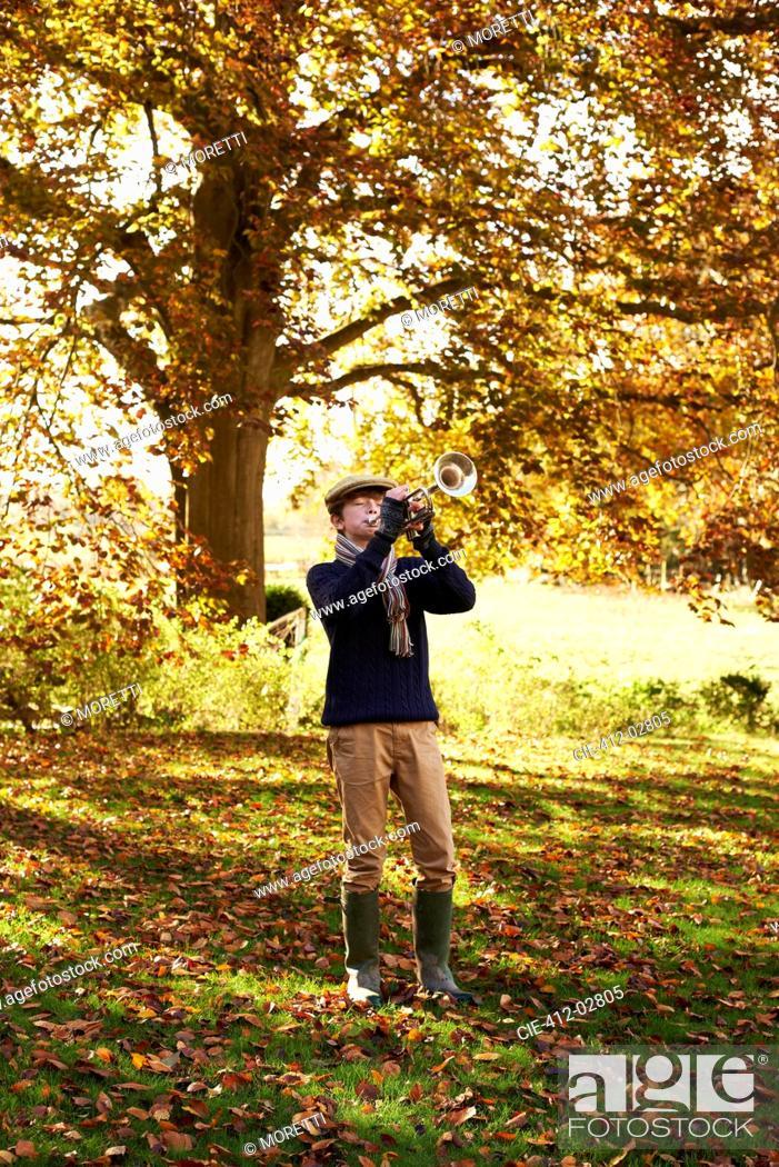 Stock Photo: Teenage boy playing trumpet outdoors.