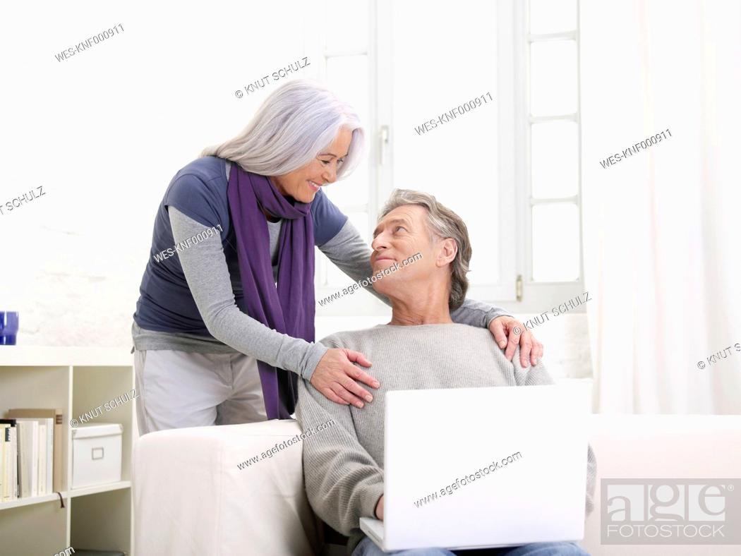 Stock Photo: Germany, Hamburg, Senior couple with laptop looking at eachother, smiling.