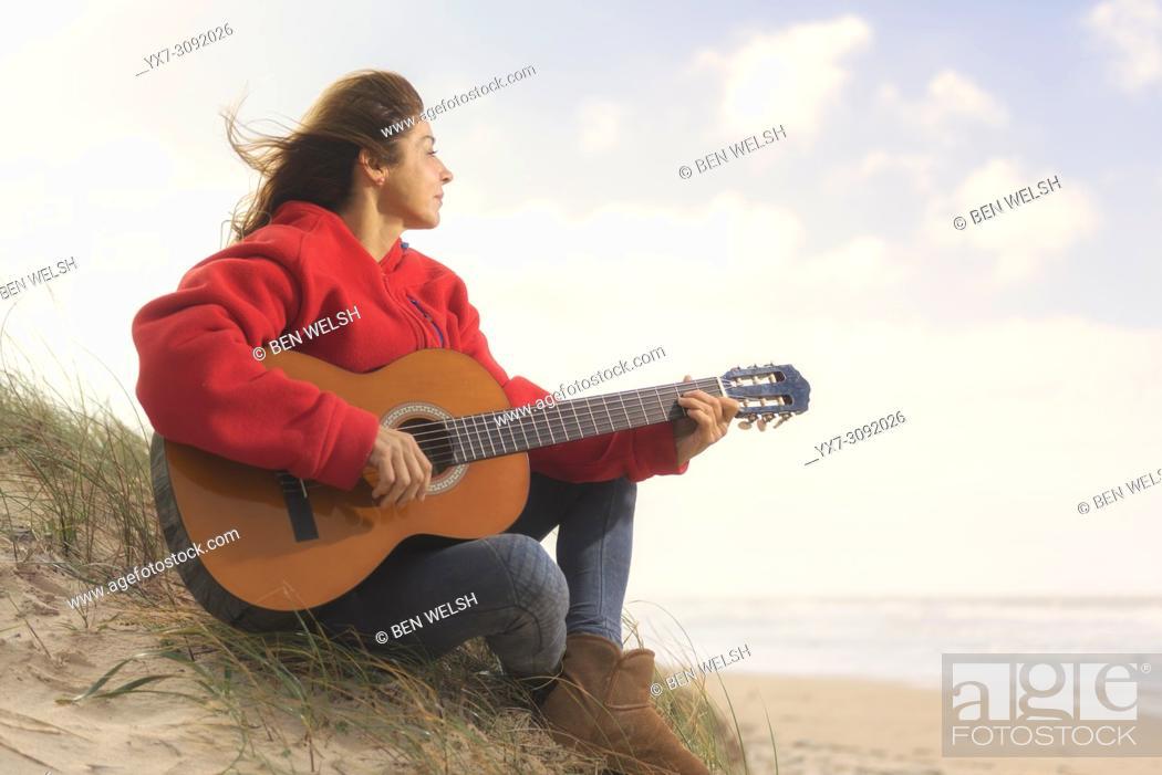 Stock Photo: Woman playing her guitar at the beach. Tarifa, Costa de la Luz, Cadiz, Andalusia, Spain.