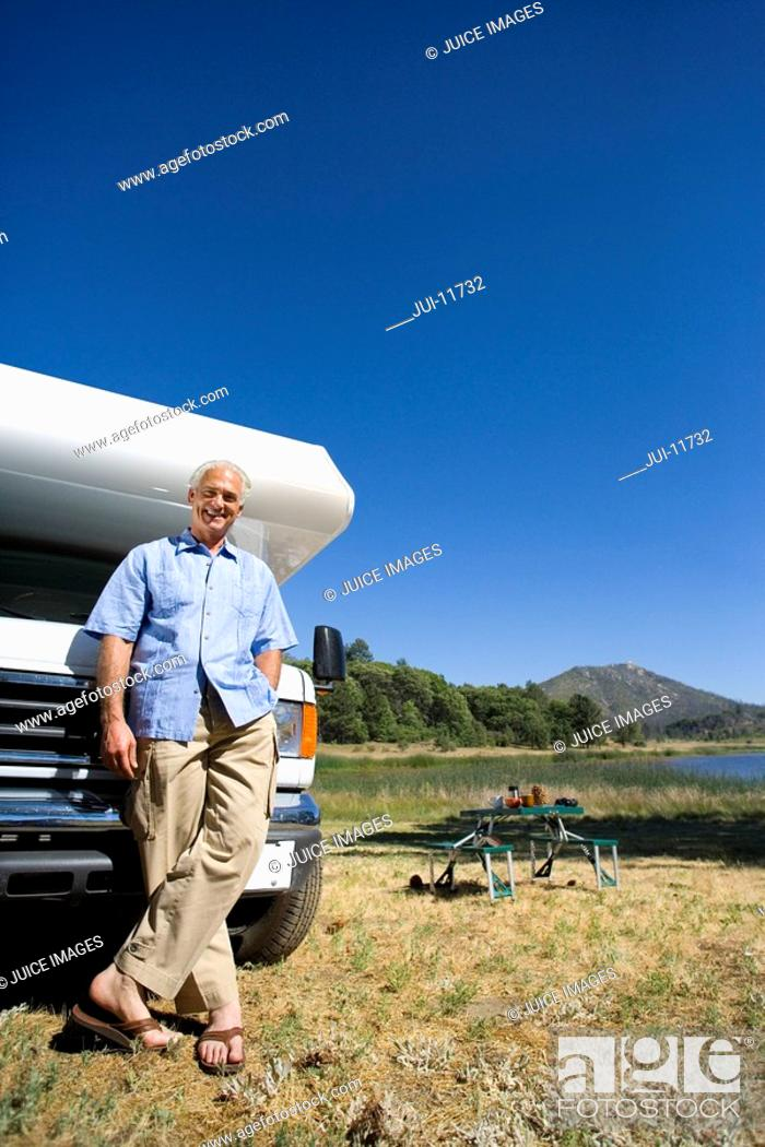 Stock Photo: Mature man by motor home and portable picnic table, smiling, portrait, low angle view.