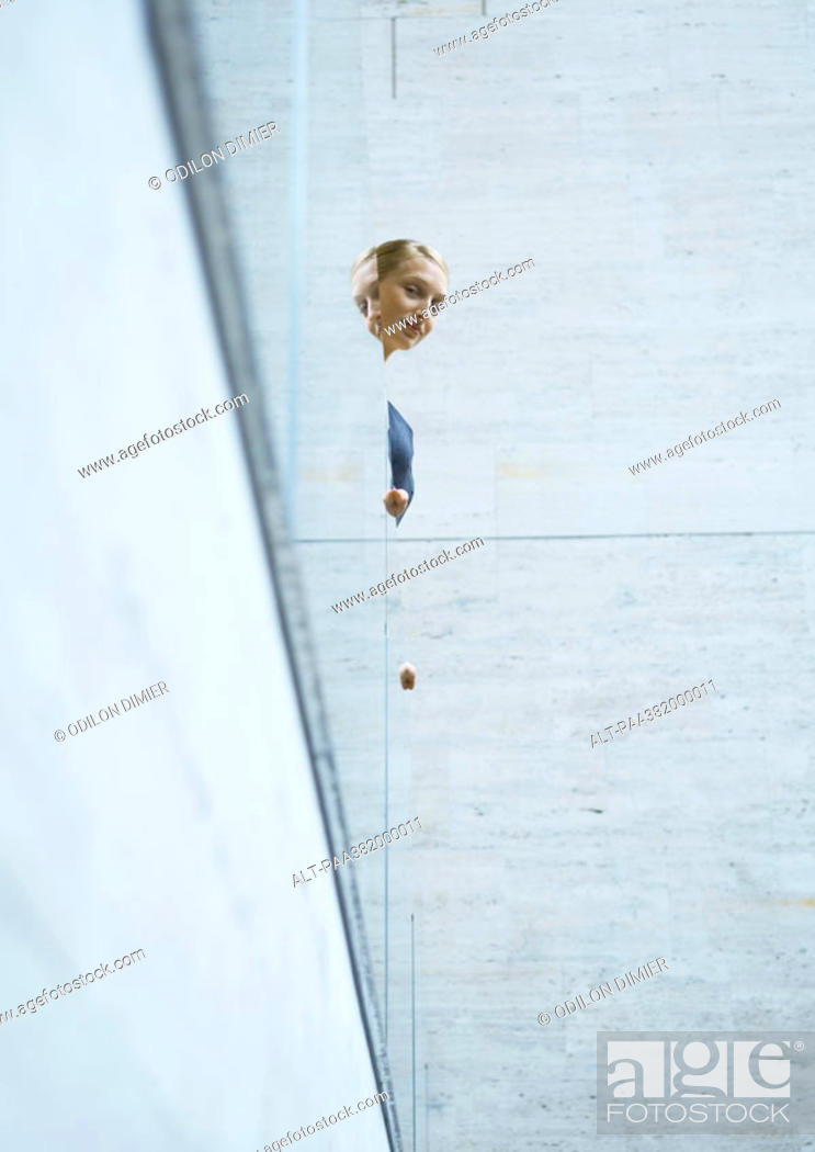 Stock Photo: Woman looking over edge of balcony.