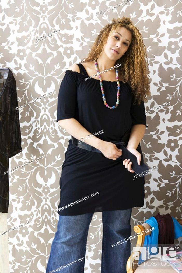 Stock Photo: Woman looking at camera adjuting belt.