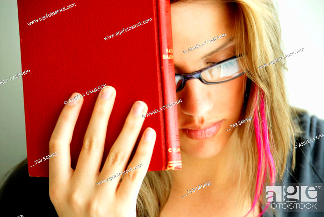 Stock Photo: 20 yr old young woman holding red book on forehead.