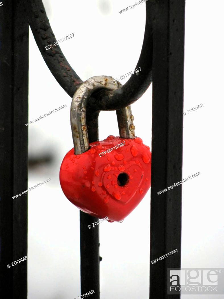 Stock Photo: Red heart lock with the drops of rain. Metal fence.