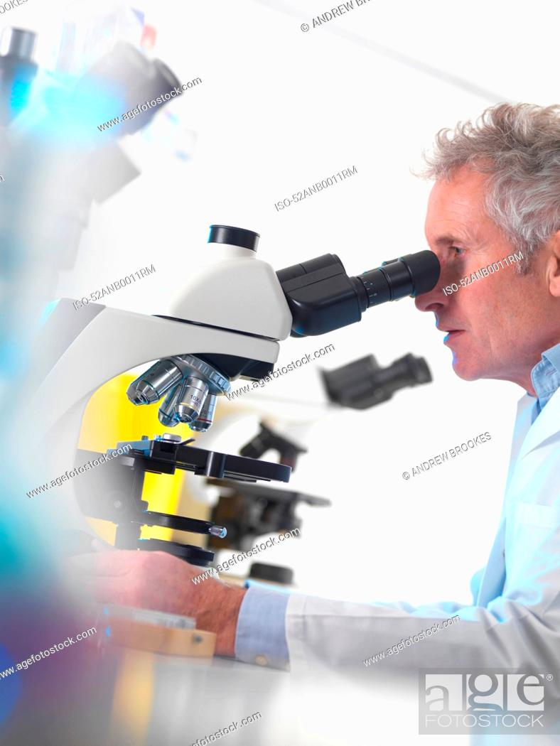 Stock Photo: Scientist using microscope in lab.
