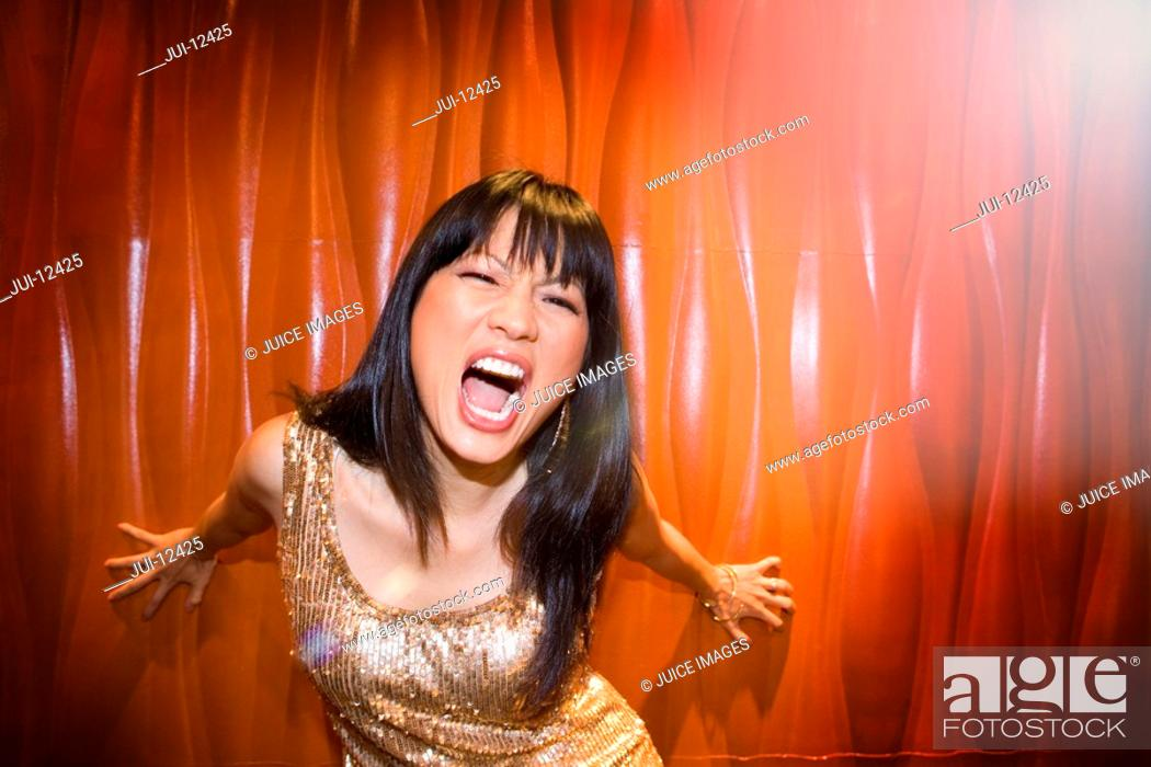 Stock Photo: Young woman in spotlight making face, close-up.