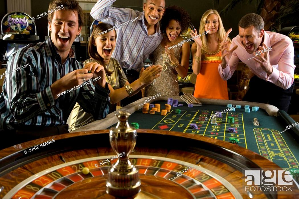Stock Photo: Men and women gambling at roulette table in casino, smiling, elevated view.