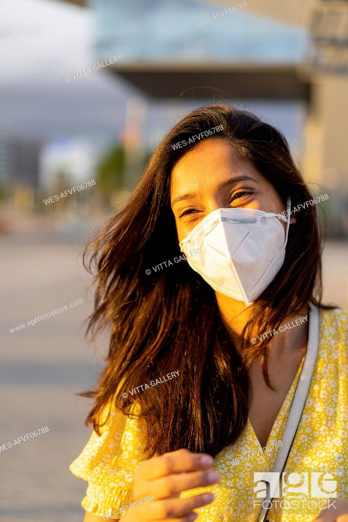 Imagen: Happy young woman wearing face mask in city.