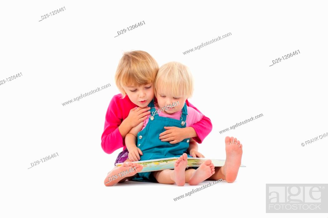 Stock Photo: sisters looking at chidren's book - isolated on white.