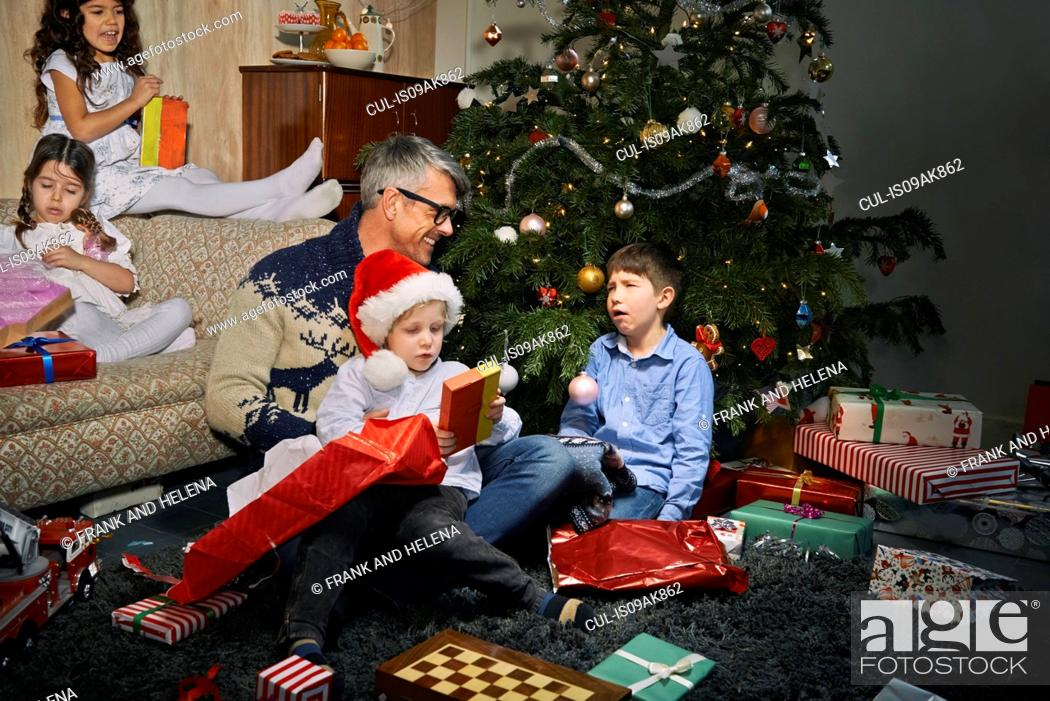 Stock Photo: Father on sitting room floor opening christmas gifts with children.