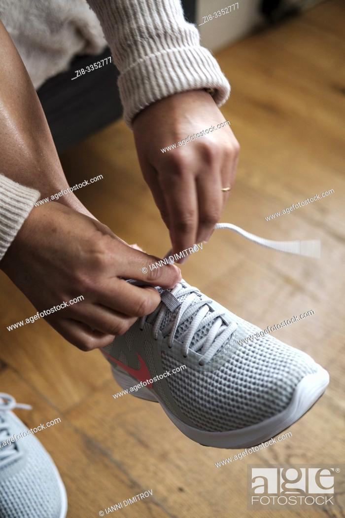 Stock Photo: Getting ready for morning jog- woman tying shoe laces- detail.