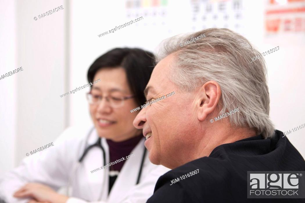 Stock Photo: Senior-aged man taking medical exam and smiling with the doctor.