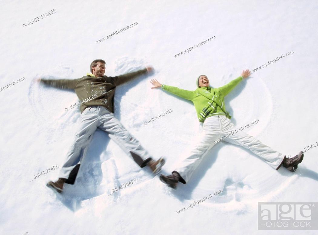 Stock Photo: High angle view of a young couple making snow angels.