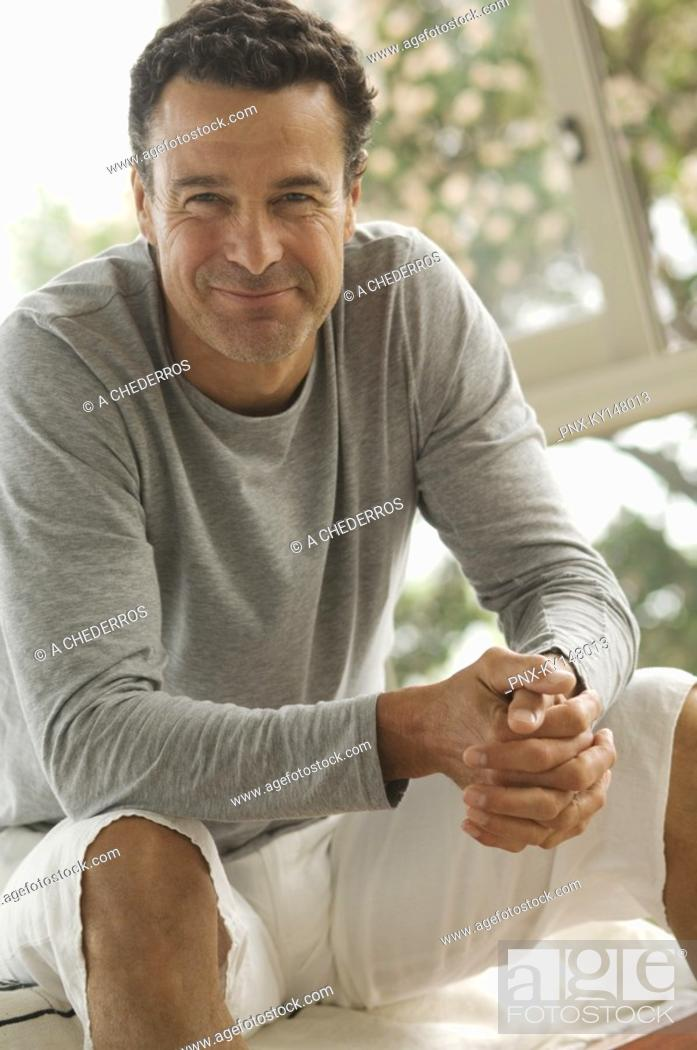 Stock Photo: Man sitting, smiling for camera.